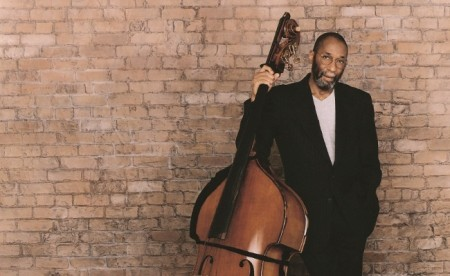 An image of Ron Carter standing by a brick wall with an upright bass.