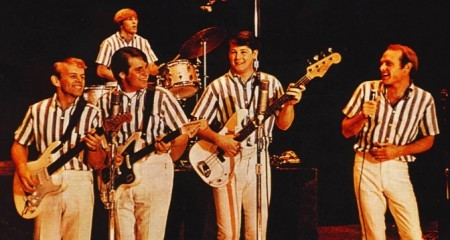 An image of the Beach Boys in blue striped shirts performing on stage as Musical Influences and Inspirations.