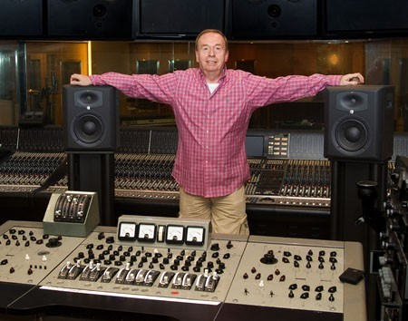 An image of Geoff Emerick in a red shirt in between two speakers and an old musical mixing console.