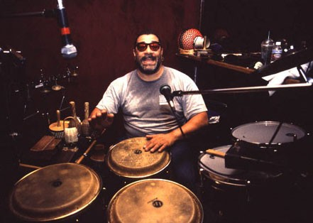 An image of Lenny Castro playing three congas.