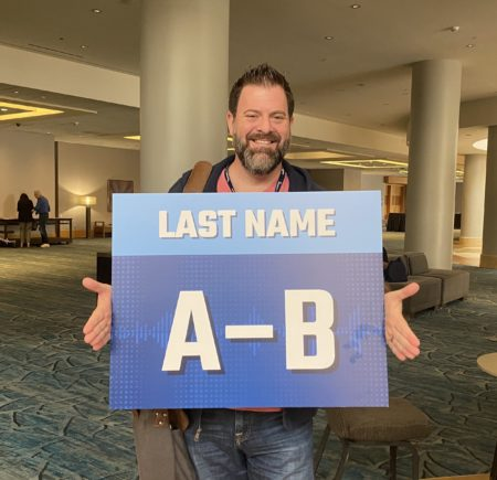 loren weisman holding a sign that reads last name, a to b with a hotel in the background.