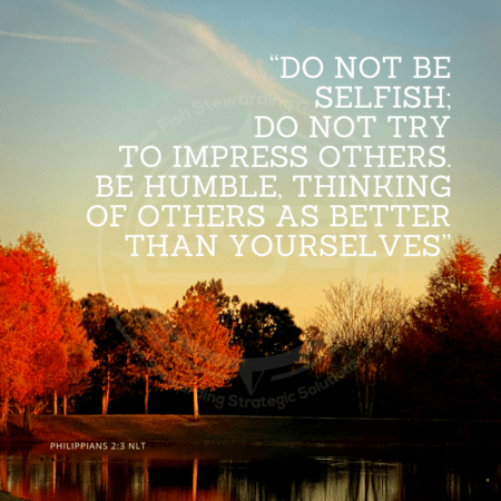 "A quote graphic with a background of orange and dark green trees at sunset with a small pond in front with a clear sky above with one whispy cloud. In center is an FSG logo watermark and a quote in white text that is credited to Philippians 2:3 NLT in a small font on the bottom and in the upper right center the quote reads, """"Do not be selfish; do not try to impress others. Be humble, thinking of others as better than yourselves."""