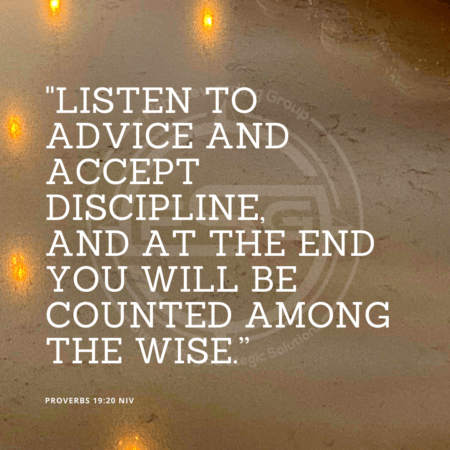 "A quote graphic with a background of a wall and a marble counter top with some lights reflecting on it. In center is an FSG logo watermark and a quote in white text that is credited to Proverbs 19:20 NIV in a small font on the bottom left and in the upper right center the quote reads, ""Listen to advice and accept discipline, and at the end you will be counted among the wise."""