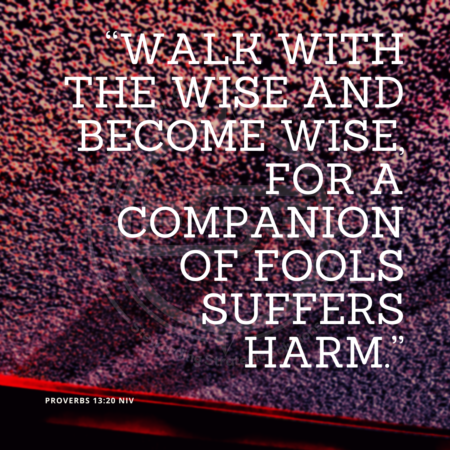 "A quote graphic with a background of light red and purple dots with a red line on the bottom. In center is an FSG logo watermark and a quote in white text that is credited to Proverbs 13:20 NIV in a small font on the bottom left and in the upper right center the quote reads, ""Walk with the wise and become wise, for a companion of fools suffers harm."""
